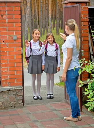 Mother waving kids off to school