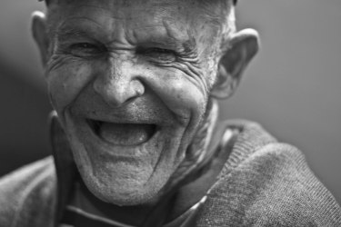 adult black-and-white close-up elder elderly eye face facial expression happy laughing man portrait sepia smile